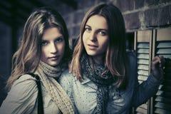 Dos muchachas de la moda de los jóvenes al lado de la pared de ladrillo Foto de archivo
