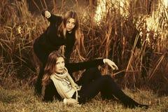 Dos muchachas de la moda de los jóvenes por el lago Imágenes de archivo libres de regalías