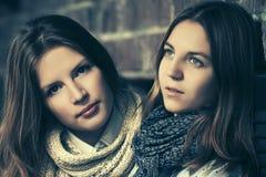 Dos muchachas de la moda de los jóvenes al lado de la pared de ladrillo Imagen de archivo