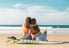 Dos muchachas de la persona que practica surf en la playa Fotografía de archivo libre de regalías