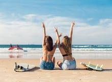 Dos muchachas de la persona que practica surf en la playa Foto de archivo