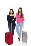 Dos muchachas de los amigos con las maletas del viaje Foto de archivo libre de regalías