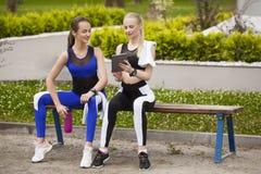 Dos muchachas de los deportes durante una rotura que mira la tableta Fotos de archivo libres de regalías