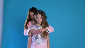 Dos muchachas de moda ríen el abrazo metrajes