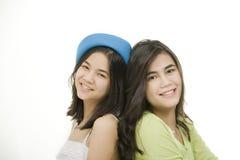 Dos muchachas de nuevo a la parte posterior, sonriendo Foto de archivo