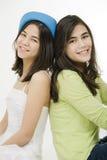 Dos muchachas de nuevo a la parte posterior, sonriendo Imagenes de archivo