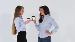 Dos muchachas de oficina atractivas sonrientes en camisas que hablan y que beben el café metrajes