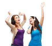 Dos muchachas de risa con el baile de los auriculares Imagenes de archivo