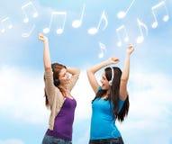 Dos muchachas de risa con el baile de los auriculares Imágenes de archivo libres de regalías