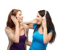 Dos muchachas de risa con los auriculares Fotos de archivo