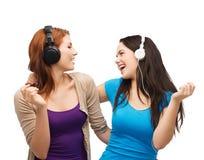 Dos muchachas de risa con los auriculares Imágenes de archivo libres de regalías
