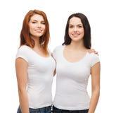 Dos muchachas de risa en el abrazo blanco de las camisetas Imagen de archivo
