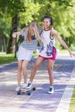Dos muchachas de risa felices Longboard patinador del adolescente junto en parque Fotos de archivo