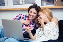 Dos muchachas de risa que miran película Imagen de archivo libre de regalías