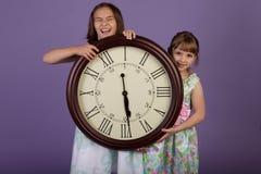 Dos muchachas de risa que sostienen un reloj de pared grande Imagen de archivo