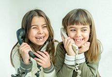 Dos muchachas de siete años que hablan en el viejo vintage llaman por teléfono con Fotos de archivo