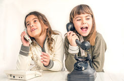 Dos muchachas de siete años que hablan en el viejo vintage llaman por teléfono con Fotos de archivo libres de regalías