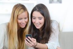 Dos muchachas del adolescente con el teléfono móvil en el sofá Fotos de archivo libres de regalías