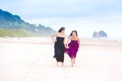Dos muchachas del adolescente que corren en la playa en día nublado fresco Fotos de archivo