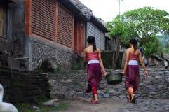 Dos muchachas del balinese que llevan un cubo Fotos de archivo
