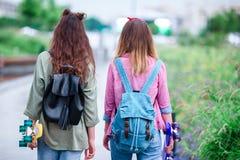 Dos muchachas del inconformista con el monopatín al aire libre en luz de la puesta del sol Skatebords del primer en manos femenin Fotografía de archivo