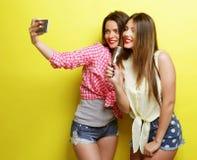 Dos muchachas del inconformista de la belleza con un micrófono toman selfi Fotografía de archivo