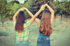 Dos muchachas del mejor amigo que hacen una muestra del forever Fotos de archivo libres de regalías