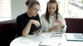 Dos muchachas del negocio en vidrios sientan y discuten negocio, utilizan una tableta y un ordenador portátil, gráficos del drena almacen de metraje de vídeo