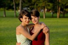 Dos muchachas del pelo corto que abrazan afuera Imagen de archivo libre de regalías