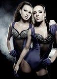 Dos muchachas del 'strip-tease' sobre fondo oscuro Fotos de archivo
