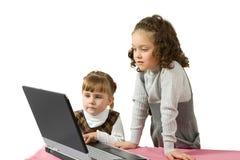 Dos muchachas delante de la computadora portátil Foto de archivo libre de regalías