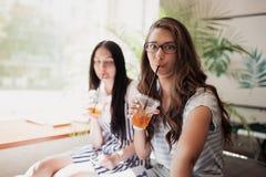 Dos muchachas delgadas hermosas sonrientes jóvenes con el pelo oscuro largo, ropa casual que lleva, se sientan uno al lado del ot fotografía de archivo libre de regalías