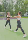 Dos muchachas deportivas que hacen ejercicios en el patio Fotografía de archivo libre de regalías
