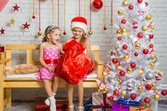 Dos muchachas descubren un bolso de regalos Fotos de archivo libres de regalías
