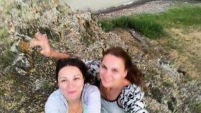 Dos muchachas despreocupadas hermosas que toman el selfie con un tel?fono elegante Las mujeres hacen caras divertidas Modelos pos almacen de metraje de vídeo