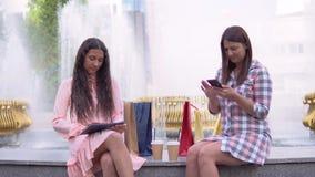 Dos muchachas después de que haga compras se estén sentando en el parque cerca de la fuente usando un teléfono y una tableta que  metrajes