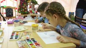 Dos muchachas dibujan en sus escritorios en la lección de dibujo almacen de metraje de vídeo