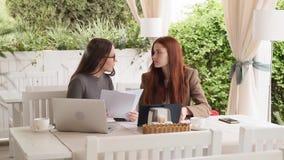 Dos muchachas discuten nuevo proyecto del negocio mientras que almorzando en la cámara lenta del café almacen de metraje de vídeo