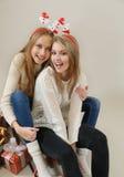 Dos muchachas divertidas en el trineo con los regalos Imagenes de archivo