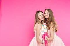 Dos muchachas dulces les gustan las muñecas que presentan en el estudio rosado con la melcocha Imagen de archivo