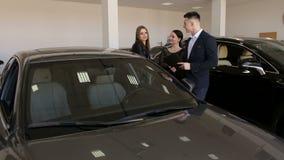 Dos muchachas eligen un nuevo coche con la ayuda del vendedor en la sala de exposición almacen de metraje de vídeo
