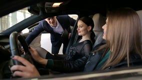 Dos muchachas eligen un nuevo coche con la ayuda del vendedor en la sala de exposici?n almacen de video