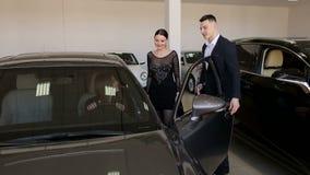 Dos muchachas eligen un nuevo coche con la ayuda del vendedor en la sala de exposici?n metrajes