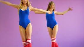Dos muchachas en bañadores azules bailan contra la perspectiva de una pared púrpura Las muchachas en el estilo del disco son bail almacen de video