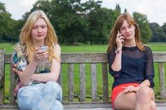 Dos muchachas en banco en parque que llaman el móvil Imagen de archivo libre de regalías