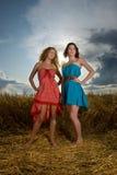 Dos muchachas en campo de trigo en puesta del sol Fotos de archivo