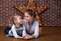 Dos muchachas en casa en pared de ladrillo delantera y estrella decorativa Fotografía de archivo libre de regalías