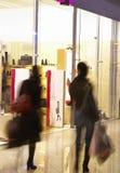Dos muchachas en centro comercial cerca de una mostrar-ventana del departamento Foto de archivo