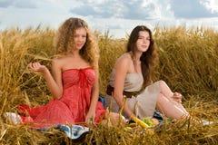 Dos muchachas en comida campestre en campo de trigo Foto de archivo libre de regalías