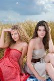 Dos muchachas en comida campestre en campo de trigo Fotografía de archivo libre de regalías